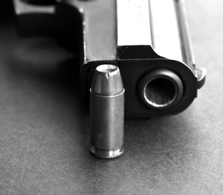 A single 40 caliber hollow point bullet laying next to the muzzle of a black pistol on a black background shown in black and white