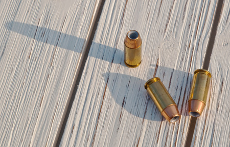 Three hollow point 40 caliber bullets on a wooden table casting their shadow upon the table