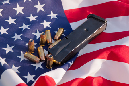 A black pistol magazine with 40 caliber hollow point bullets shown surrounded by an American flag