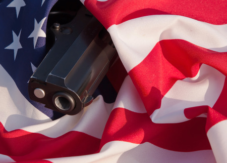 A black pistol's muzzle seen protruding wrapped in an American flag