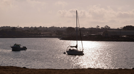 A sailboat and a fishing boat in a bay in the morning sun in southern California, USA Stock fotó