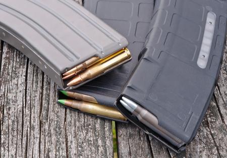 Trois magazines de fusil contenant différents types de balles de calibre .223 avec un fond en bois