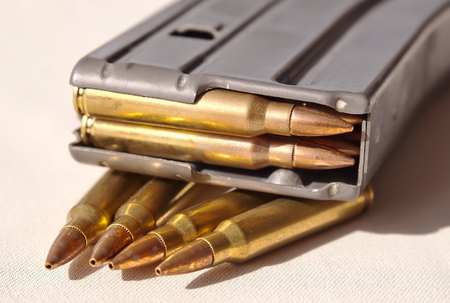 A metal rifle magazine loaded with .223 caliber bullets laying on top of four bullets of the same caliber 写真素材 - 112276538