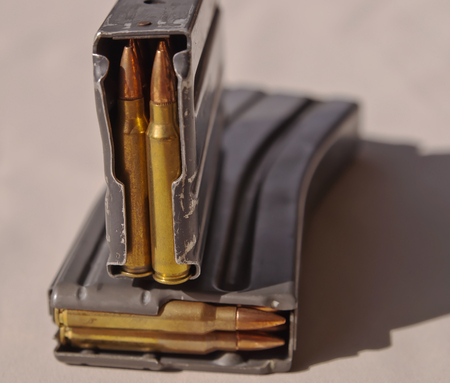 Two metal rifle magazines, one stacked upon the other, loaded with .223 caliber bullets