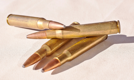Four 30.06 caliber bullets together on a white background showing shadows