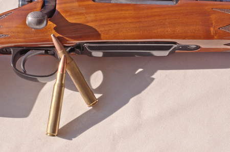 A wooden 30.06 rifle laying on it's side on a white background with two rifle bullets leaning against it