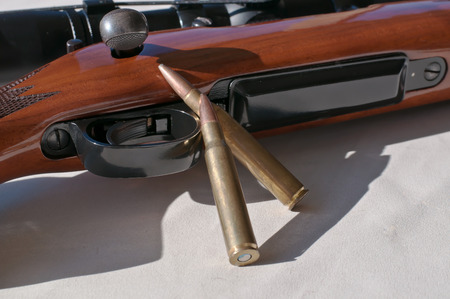 A wooden 30.06 rifle laying on its side on a white background with two rifle bullets leaning against it