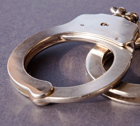 Metal handcuffs shown on a black background
