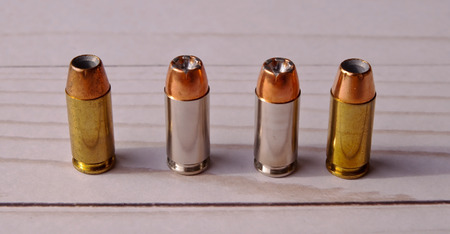 Four 40 caliber hollow point lined up on a white wooden back ground, the bullets have different cases, some silver and the other brass