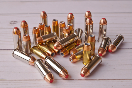 A group of 40 caliber hollow point and 44 special bullets together on a white wooden back ground