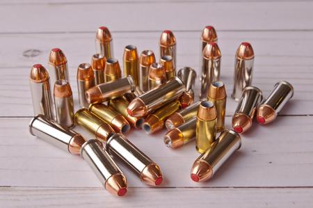 Un groupe de pointe creuse de calibre 40 et 44 balles spéciales ensemble sur un fond en bois blanc