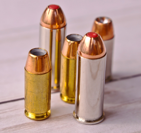 Five bullets, two 44 special and three 40 caliber hollow points on a white wooden back ground Stock Photo