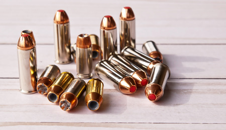 Sixteen bullets, eight 40 caliber hollow points and eight 44 special red tipped ones on a white wooden background