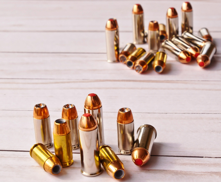 Two sets of 40 caliber bullets and 44 special bullets on a white wooden background. The set in the background is slightly blurred, spotlighting the one in the foreground