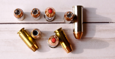 Six 40 caliber hollow point bullets along with three 44 special red tipped bullets shot from above on a white wooden background