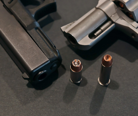A black pistol with a 40 caliber hollow point in front of it next to a stainless revolver with a 357 caliber hollow point bullet in front of it on a black background