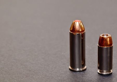 A 40 caliber hollow point bullet and a 44spl red tipped bullet  together on a gray background with room for text 免版税图像