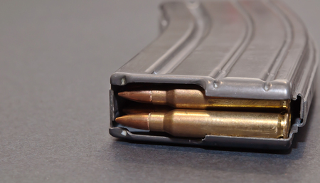 A rifle magazine loaded with .223 bullets on a gray background 写真素材