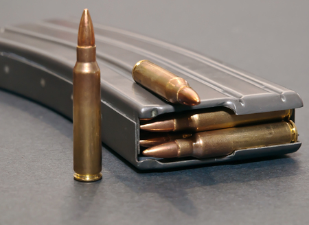A rifle magazine loaded with .223 bullets on a gray background with two extra bullets
