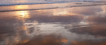 The shallow surf of the Pacific ocean in southern California, USA with the clouds reflecting off the water and sand at sunset