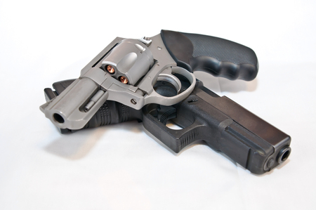 Two handguns, a silver 357 magnum revolver on top of a black 9mm pistol on a white background