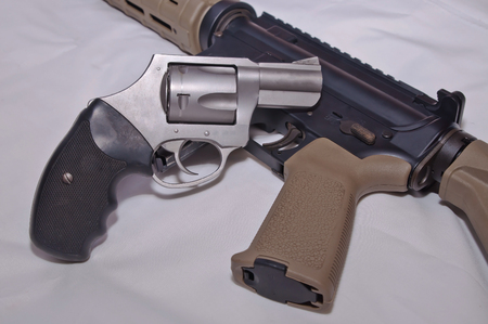 A stainless steel 357 magnum revolver with a black grip on top of a black and brown 223 caliber AR-15 rifle with a white background