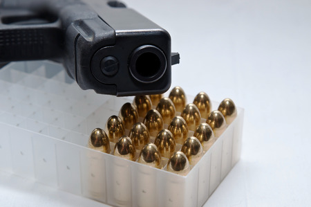 A black semiautomatic 9mm pistol laying on top of a plastic bullet case filled with twenty gold, full metal jacket bullets on a white background