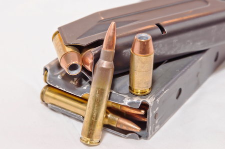A loaded handgun magazine with 40 caliber bullets and a loaded rifle magazine with .223 caliber bullets along with each of those bullets on the magazines on a white background Banco de Imagens