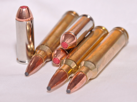 Six different bullets, a .300 Winchester Magnums for a rifle and a .44 specials for a handgun on a white background Stock Photo
