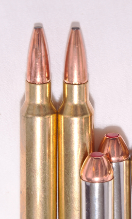 Four different bullets, a .300 Winchester Magnums for a rifle and a .44 specials for a handgun on a white background Stock Photo