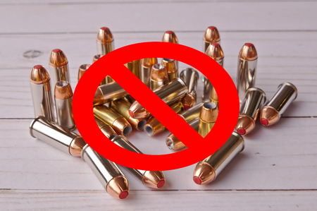 A red circle with a line meaning banned over a set of handgun bullets on a wooden background