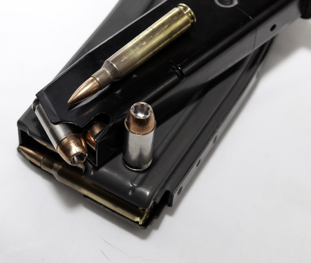 Two magazines, one for a pistol and one for a rifle both loaded with bullets with a 40 caliber and 223 caliber shown on top of them on a white background