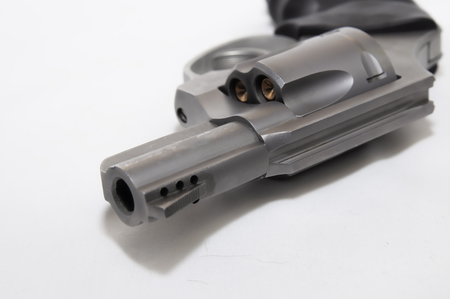 A loaded 357 magnum stainless revolver laying in its side on a white background