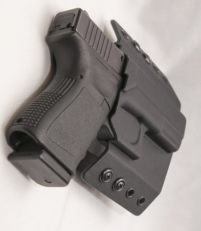 A black 9mm pistol in a black holster isolated on a whtie background