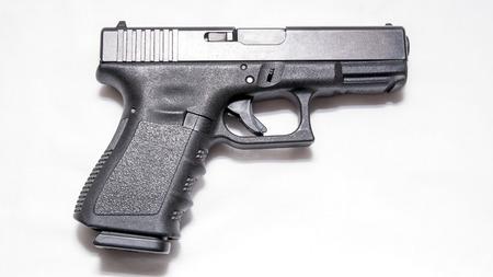 Una pistola de 9 mm negra aislada sobre un fondo blanco.