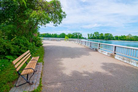 Pittsburgh, Pennsylvania, USA 06/09/2019 A walkway around the Highland Park Reservoir on a bright spring day with a bench in the shade 新聞圖片