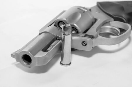 A loaded 357 stainless steel revolver with a hollow point bullet next to it shot in black and white 版權商用圖片
