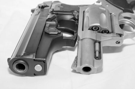 Two handguns, a 40 caliber pistol and a 357 magnum revolver shot in black and white