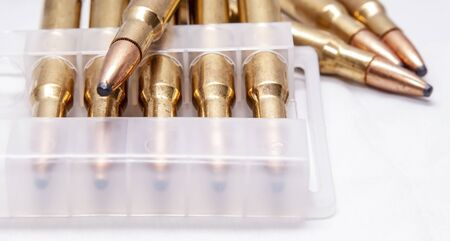 A close up of brass rifle bullets used for hunting, some in a plastic case on a white background 版權商用圖片