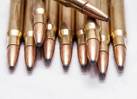 A close up of brass rifle bullets used for hunting on a white background