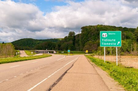 A Pennsylvania Department of Transportation road sign along State Route 6 for the exit for State Route 62 to Tidoute and Tionesta in Warren County, Pennsylvania, USA