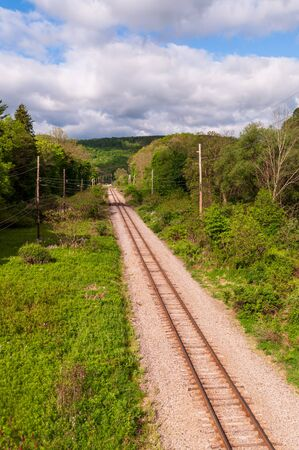 Train tracks through the woods on a sunny spring day in Warren County, Pennsylvania, USA