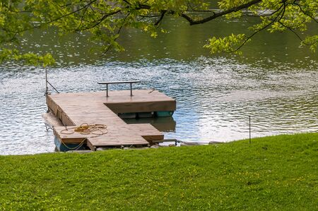 A wooden boat dock on the Allegheny River on a sunny summer day in Warren County, Pennsylvania, USA