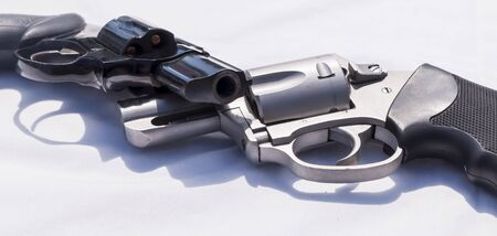 Two handguns, a stainless steel 357 and a black 38 special revolver on a white background