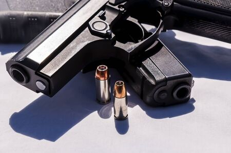 Two black semi automatic pistols, a 40 caliber and a 9mm with a hollow point bullet for each next to them on a white background