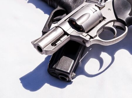 Two handguns, a 357 magnum revolver on top of a 9mm pistol on a white background