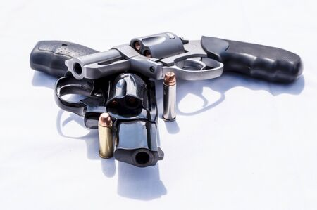 Two revolvers, a 357 magnum and a 38 special with hollow point bullets for each of them on a white background
