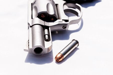A stainless snub nosed 357 magnum revolver with a hollow point bullet next to it on a white background