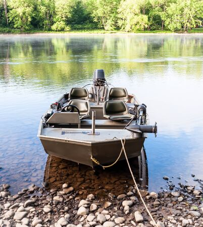 A recreational fishing boat moored to the riverbank on the Allegheny River in Warren County, Pennsylvania, USA on a sunny day