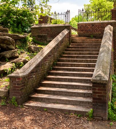 Concrete steps lined with a brick wall leading up to a landing with a wrought iron fence in Mellon Park, Pittsburgh, Pennsylvania, USA
